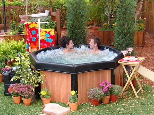 man and woman relaxing in a hot tub in the garden