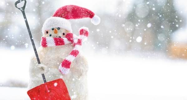Snowman ready for snow with santa hat and show shovel