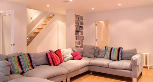 Basement with large u shape sofa and colourful cushions for comfortable  home extension ideas