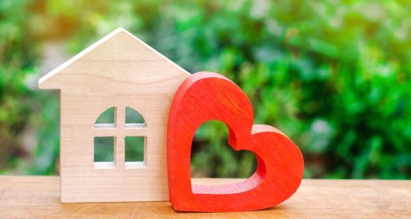 model wooden house and heart to represent loving your home.
