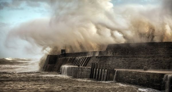 Storm wave breaking over a sea wall