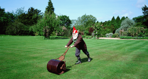 Man in a gnome outfit mowing the lawn