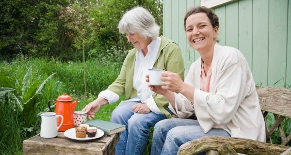 two ladies sitting outside a shed having a cup of tea