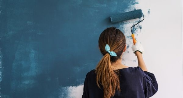 female painting a wall in a blue colour