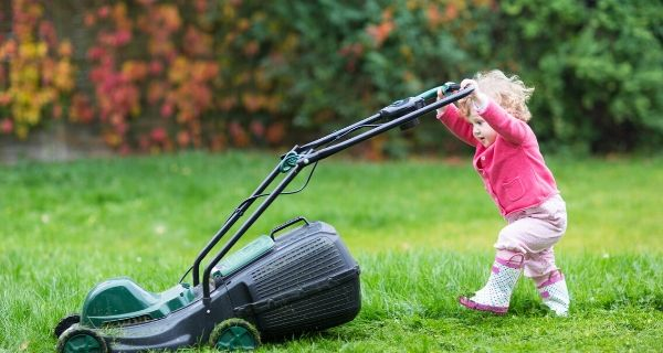 child pushing lawn mower