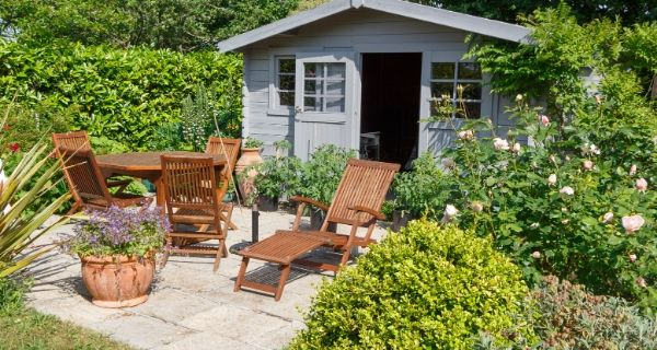 painted garden shed surrounded by table and chairs and green shrubs
