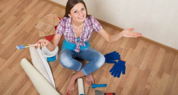 Woman with decorating items around her while sat on a floor
