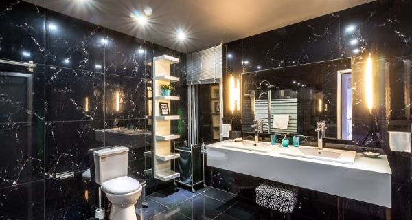 black tile bathroom that is a wet room and has lights around a large mirror