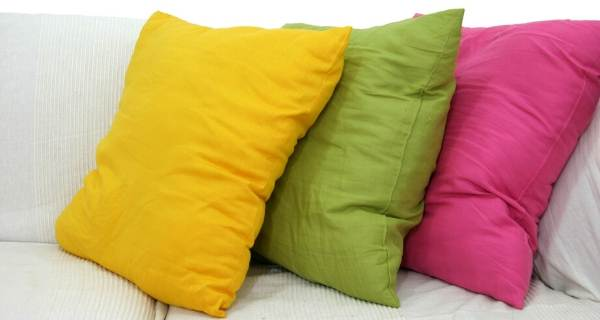 yellow green and pink cushions on sofa
