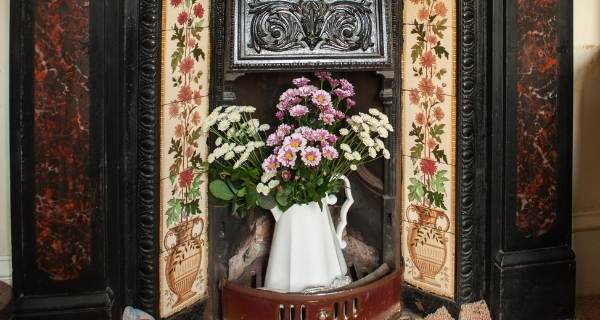 victorian fireplace with flowers inside it