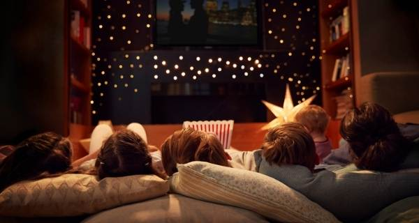 Family lay on sofa looking at TV with fairy lights for movie night