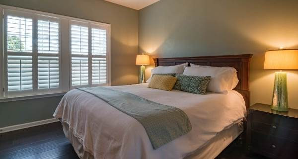 green bedroom with warm lamp lighting either side light
