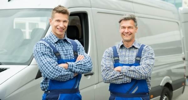 two tradesmen outside a van